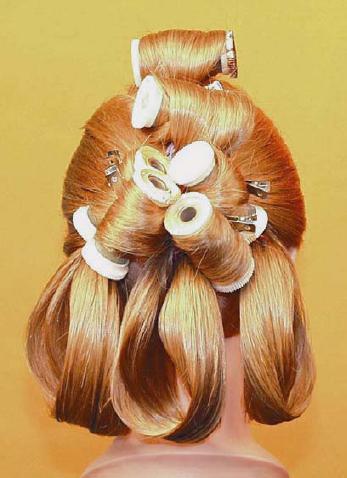 12. Разделите хвост на 4 части и накрутите на горячие бигуди.  Сбрызните лаком накрученные волосы.