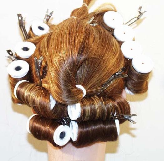 Поднимите хвост наверх вдоль и накрутите бигуди на волосы под хвостом параллельно полу как показано на фото.